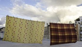 Drying bedclothes on the roof of a building royalty free stock photography