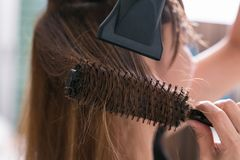 Drying blond hair with hair dryer and round brush. Royalty Free Stock Photo