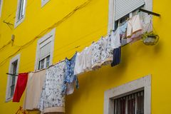 Drying clothes outside windows against yellow wall. Bright colorful building in Portugal. Traditional house exterior in Europe. Laundry on rope at the street stock image