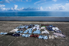 Drying clothes on the pavement at seafront. Baracoa, Cuba Royalty Free Stock Photos