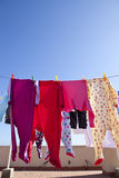 Drying clothes. Picture of kid pyjamas drying outside, on a clothesline, on a roof during a sunny day Royalty Free Stock Image