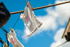 Drying clothes on a rope in sunny weather, drying of linen with a heart pattern after washing. Drying clothes on a rope in sunny weather, after washing the royalty free stock images