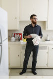 Drying Dishes. Man with beard wearing dark shirt and denim stands at his kitchen sink drying dishes Stock Photography