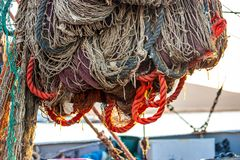 Drying fishing nets on the trawler in city harbor. At sunset of the day Stock Images