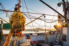 Drying fishing nets on the trawler in city harbor. At sunset of the day Stock Photo