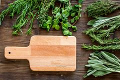 Drying fresh herbs and greenery for spice food on wooden kitchen desk background top view space for text. Drying fresh herbs and greenery for spice home food on stock photography