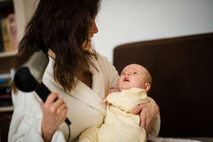 Drying hair with baby in hands Stock Photography