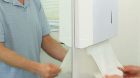 Drying Hand Skin in a Restroom. Man drying wet hands with a couple of disposable tri fold paper towels from a mounted wall dispenser in a bathroom during the stock video