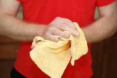 Drying Hands with Hand Towel. Adult male caucasian wearing a red shirt drying hands on a yellow cotton cloth dish towel close up Stock Photos