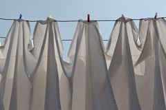 Drying the laundry. Of white table cloths in the clothesline Stock Image