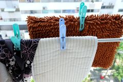 Drying mats on clotheshorse. Drying brown mat and white mat on clotheshorse that outside the room in condominium with clothespins under the sun stock images