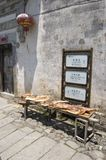 Drying meat and sign. Legs of meat drying in the sun at Hongcun, China Royalty Free Stock Images