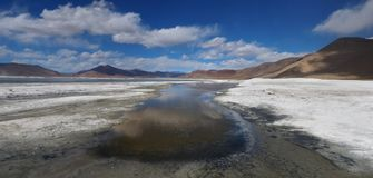 The drying mountain lake among the salt desert in the Himalayas, the blue sky has white cumulus clouds, panorama. Stock Photo