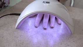 Drying nails in the UV Lamp Nail Dryer Machine. Closeup stock video
