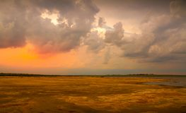 Drying out inland dam landscape with clouds stock photography