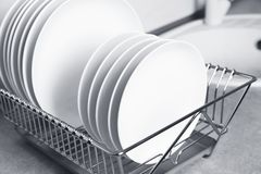 Drying rack with clean dishes on kitchen counter. Closeup royalty free stock photo