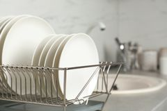 Drying rack with clean dishes on kitchen counter. Space for text royalty free stock image