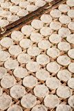 Drying rice galettes, Myanmar. A number of compressed rice cakes or galettes on a rack oute drying under the sun Royalty Free Stock Image