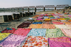 Drying sari, India. Colorful sari are dryed on the bank of river Yamuna near railway bridge in Agra in India Stock Images