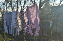 Drying shirts. Freshly washed shirts and sweats hanging on the line outdoor and drying Royalty Free Stock Photography