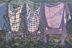 Drying laundry outdoor. Freshly washed shirts and sweats hanging on the line outdoor and drying Stock Photos