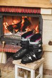 Boots ski boots in front of fireplace. Drying shoes in front of the fireplace. Two ski boots stand on a stool in front of a burning fireplace stock images