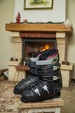 Boots ski boots in front of fireplace. Drying shoes in front of the fireplace. Two ski boots stand on a stool in front of a burning fireplace in a bright room royalty free stock photo