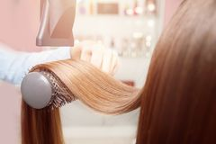 Drying and styling dryer shiny strands of dark brown hair close-up. Master in beauty salon for women stock images