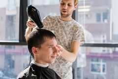 Drying, styling men`s hair in a beauty salon stock images
