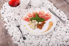 A drying thin slices of ham and basil on a white plate. A glass of red wine and meat dish on the white stone background. Royalty Free Stock Photos