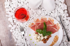 A drying thin slices of ham and basil on a white plate. A glass of red wine and meat dish on the white stone background. Royalty Free Stock Images