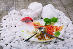 A drying thin slices of ham and basil on a white plate. A glass of red wine and meat dish on the white stone background. Royalty Free Stock Photography