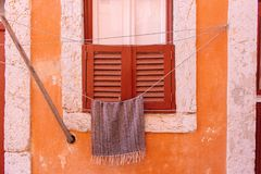 Drying towel on rope against orange weathered wall in Portugal. Closed window with shutters on old wall with drying linen. royalty free stock images