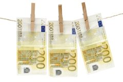 Drying Two Hundred Euro Bills. Three two hundred euro bills hanging on a clothesline. Isolated on a white background Royalty Free Stock Photos