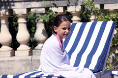 Drying up. A caucasian girl sitting on a sunbed drying up with a towel after swimming Stock Photography