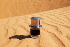 Drypa svart kaffe i vietnamesisk stil med förtätat mjölkar på en röd sand med kopieringsutrymme arkivbild