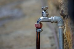 Drypa vattenkranen med den förbindelseslangen arkivfoton