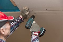 Drywall construction, attic renovation. Man fixing drywall suspended ceiling to metal frame using electrical screwdriver royalty free stock photography