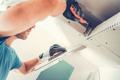 Drywall Finishing Patches. Apartment Remodeling by Caucasian Worker. Finishing Ceiling Elements stock images