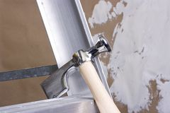 Drywall hammer. On a step ladder next to a brown drywall Royalty Free Stock Images