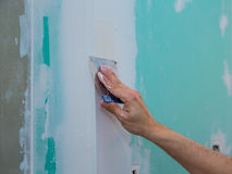 Drywall hydrophobic plasterboard trowel plastering seam. Drywall hydrophobic plasterboard in green plastering seam with trowel Stock Photography