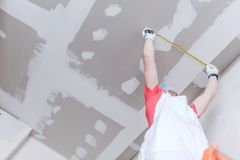 Drywall Measurement. Drywall Construction Measurement by Caucasian Worker stock photography