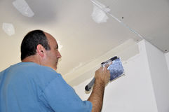 Drywall spackling. Man spackling drywall for a house renovation Stock Image