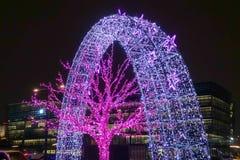 Drzewa i archways dekorowali z rozjarzonymi purpurowymi neons fotografia stock