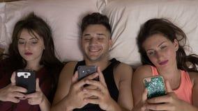 Drzewni nastoletni przyjaciele wydaje czas na ich smartphones technologii nałogu wyszukuje internet w łóżku zbiory wideo
