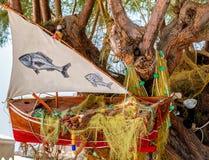 Drzewo, dekorujący z starą czerwoną łodzią rybacką Obrazy Royalty Free