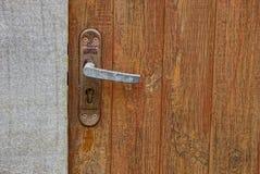 Drzwiowa rękojeść z kędziorkiem na drewnianym drzwi Zdjęcia Stock