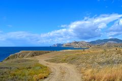 Country road along the sea on a sunny day with blue sky and clouds royalty free stock images
