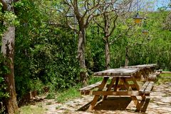 View of the resting area with tables and benches. View of rest place with wooden tables and benches in forest park. Resting area for mountaineers and other royalty free stock images