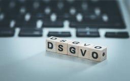"""DSGVO: Cubos de madeira com o  do """"DSGVO†das letras que encontra-se em um portátil Datenschutzgrundverordnung fotografia de stock"""